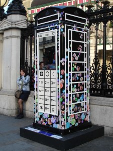 "Fred Butler's ""Mobile Phone"" design outside Charing Cross station. His is the big one in the centre of the photo (not the one in use on the left). I like the Pearly King look about it. Most fitting."