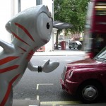 Wenlock hailing a black cab by the Novello Theatre. I hope he knows black cabs are not allowed in the Olympic lanes whilst the Games are on