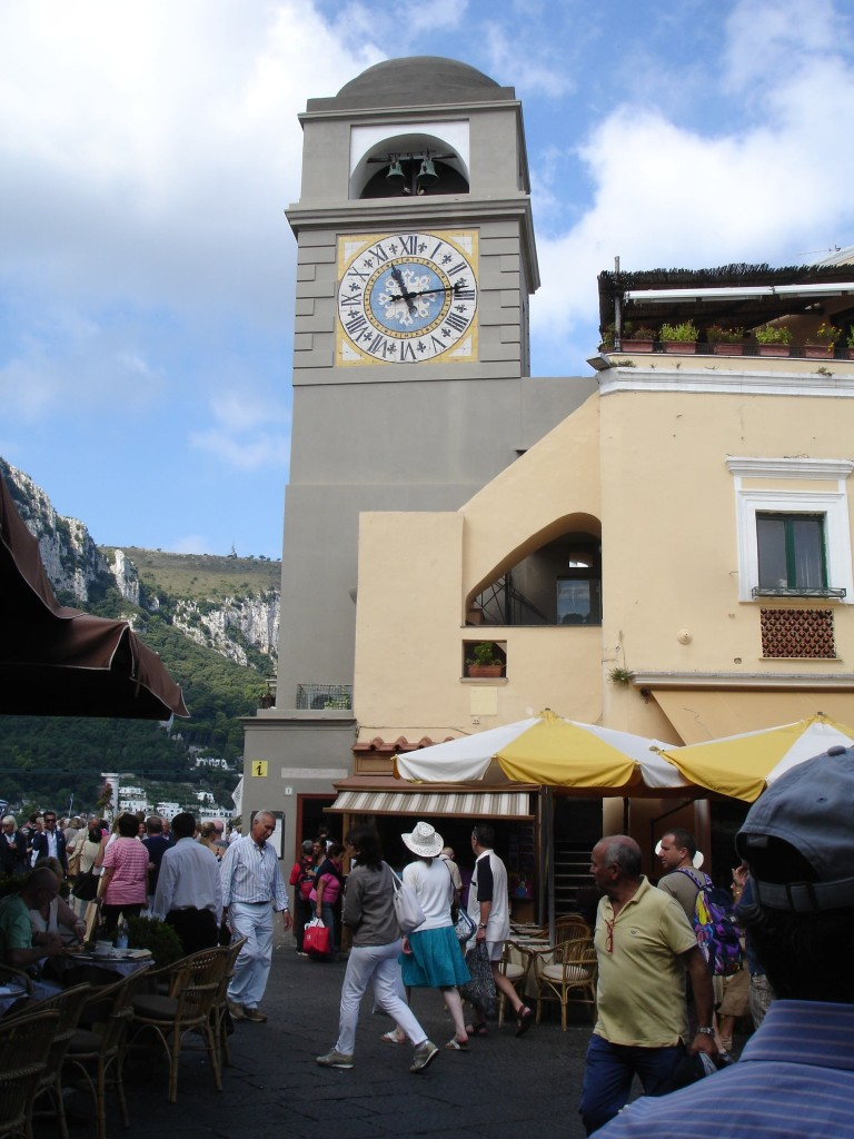 The large clock tower ... and the equally large crowds ... in Capri Town's glamorous Piazza Umberto I. Day trippers tend to stay around the harbour below or take the funicular up here to the town to peruse the posh boutiques or sip coffee in the Piazza where Bardot, Hepburn and Kennedy-Onassis once frequented