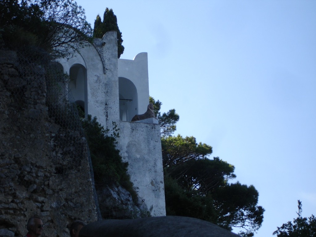 The sphinx sits right on the edge of the villa grounds and cliff top looking across the bay of Naples, and although appears not to be indigenous to the island, the creature is an enduring symbol of Capri