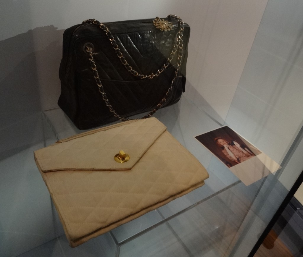 An original early 2.55 Chanel shoulder bag and clutch bag next to a photo of the queen of fashion herself