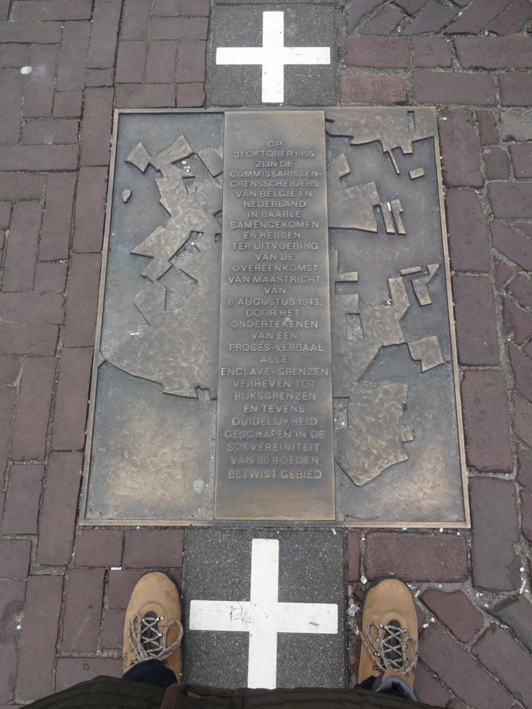 A plaque commemorating international recognition of all borderlines in Baarle, with my feet in shot (right foot in the Netherlands, left foot and coat buttons in Belgium)