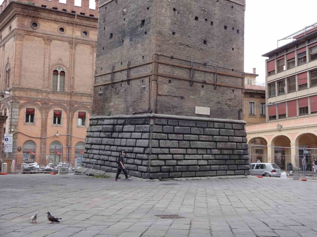Bologna Le Due Torri, Torre Garisenda base with girl walking past