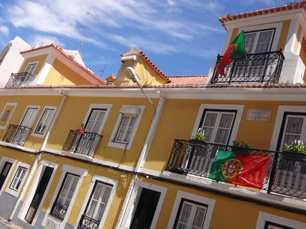A row of charming old houses in Cacilhas. Legendary Portuguese actor Antonio Feio once lived in the house marked by a plaque and Portuguese flags