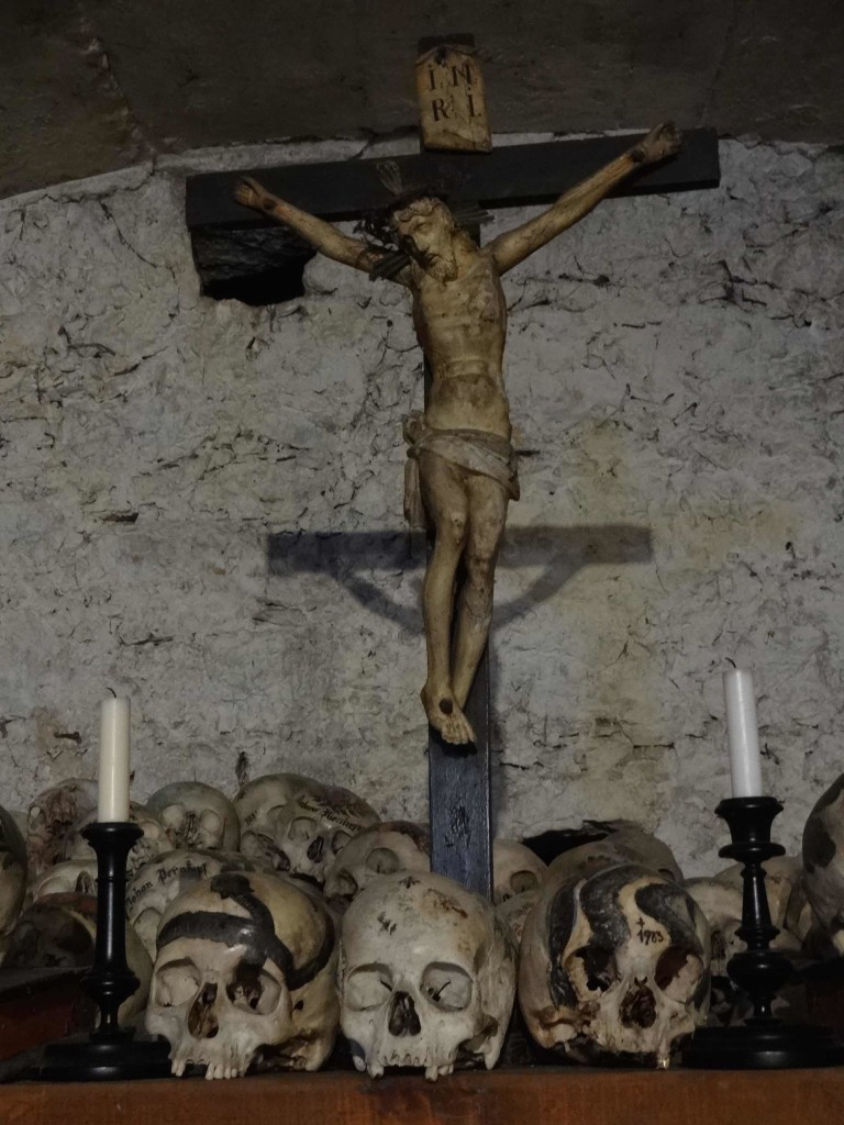 The two skulls at the foot of the Cross are painted with a snake - the symbol of Death. The snake painted skull on the right is that of a woman who died in 1983 and is the last skull to date to be laid to rest in the Beinhaus. Her gold tooth is still intact