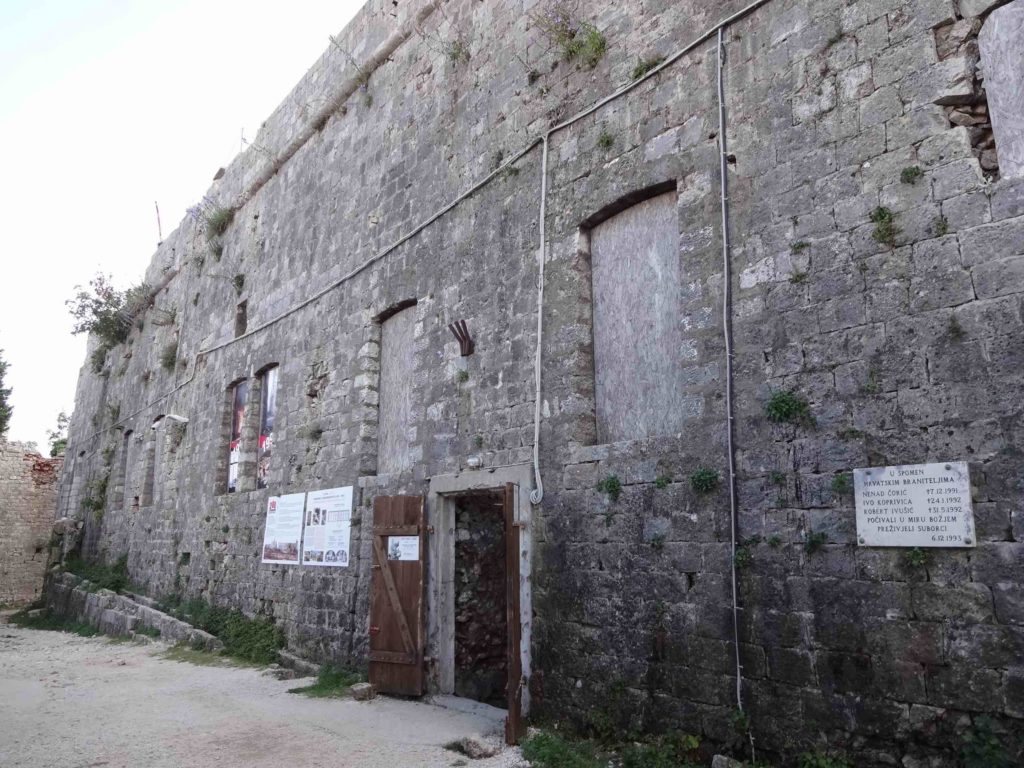 ...and partly due to the ravages of the Homeland War. The impact of one mortar can still be seen at the end of the building, and a plaque commemorating those volunteers who died here defending the city in the early 1990s can be seen on the front wall (right)