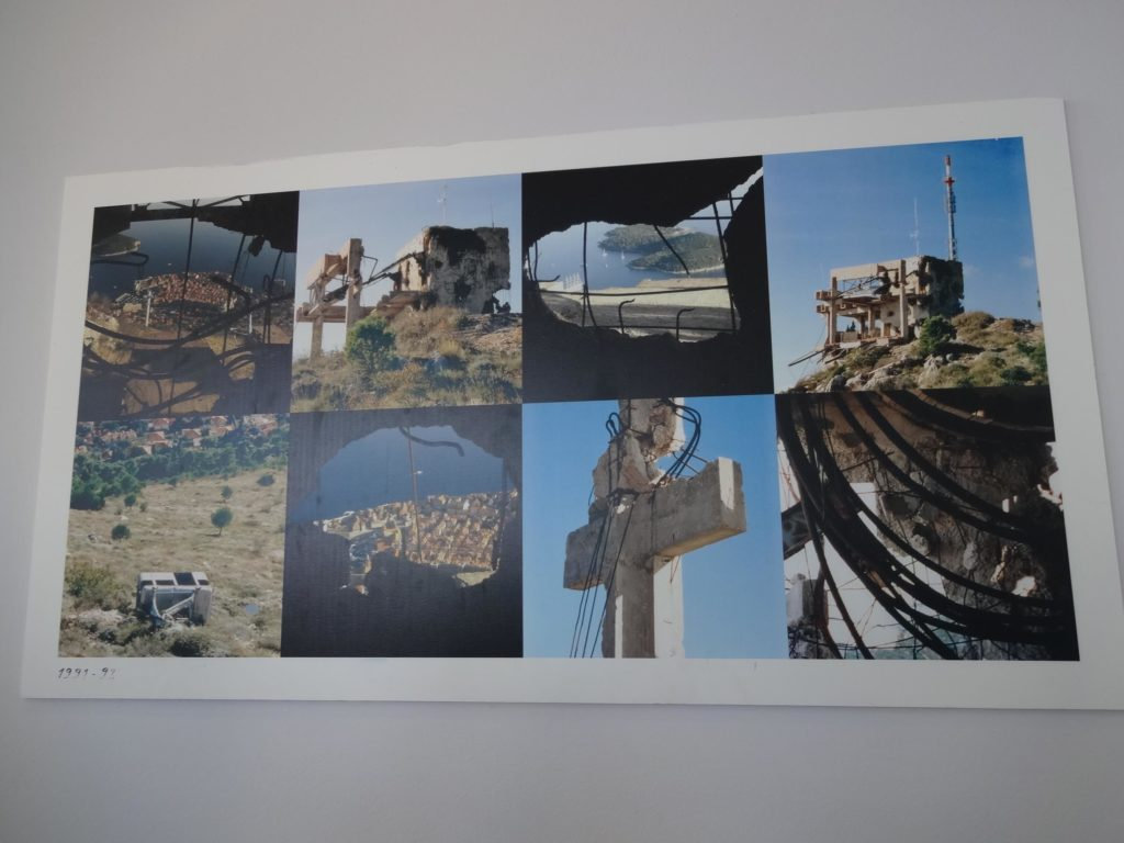 Some images on display inside the Mount Srd cable car station depicting the damage caused to the surrounding area during the siege, including the stone cross close to the station and the severing of the cable car lines