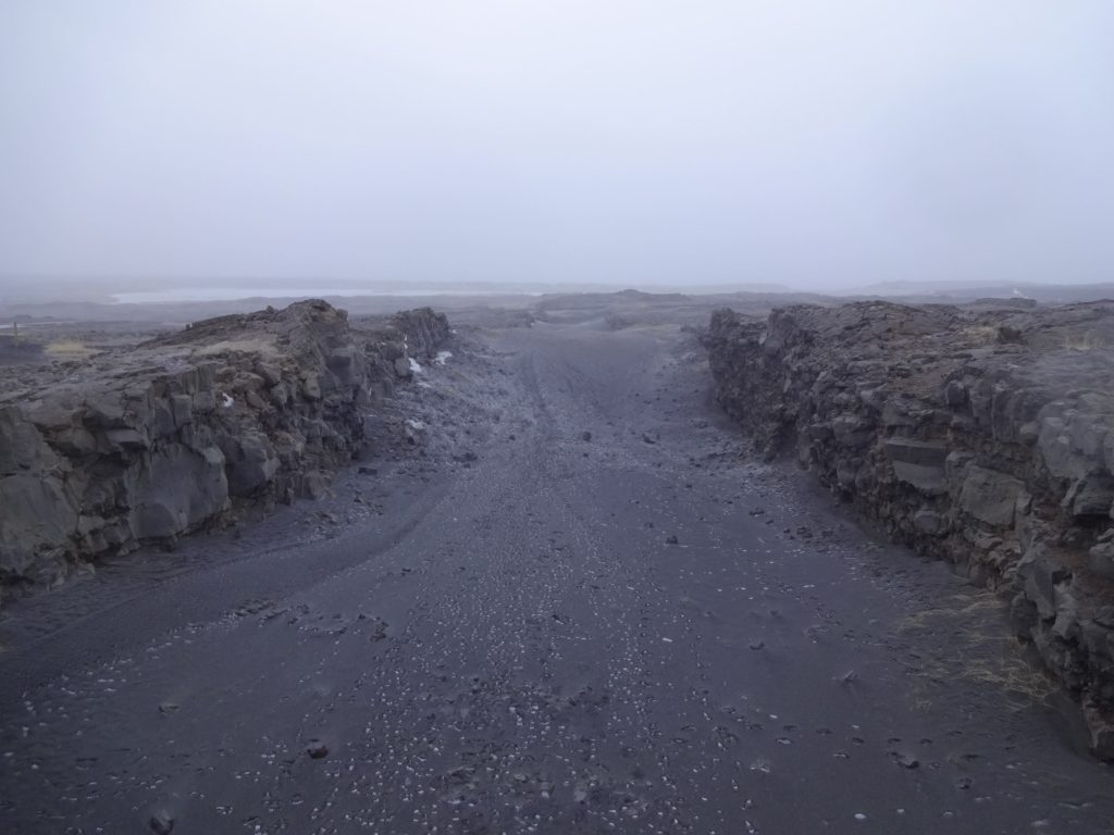 At the halfway point along the bridge. The Eurasian tectonic plate is to the left, the North American plate is to the right, and the volcanic gulf in the middle is geologically No Man's Land