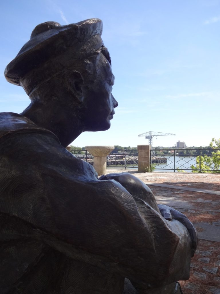"A sculpture of ""Young Jules"" by Elisabeth Cibot, looking out across the port and the Loire river that inspired his later writings"