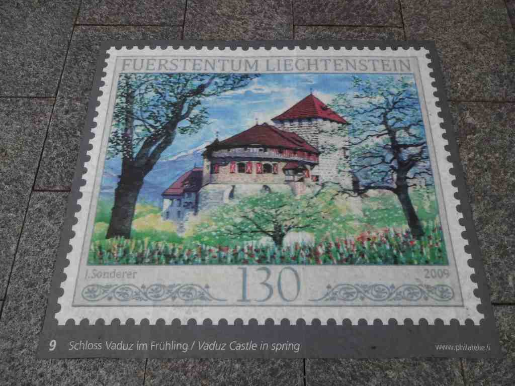 One of the square metre sized stamp reproductions outside the Post Museum along the pavement of Städtle