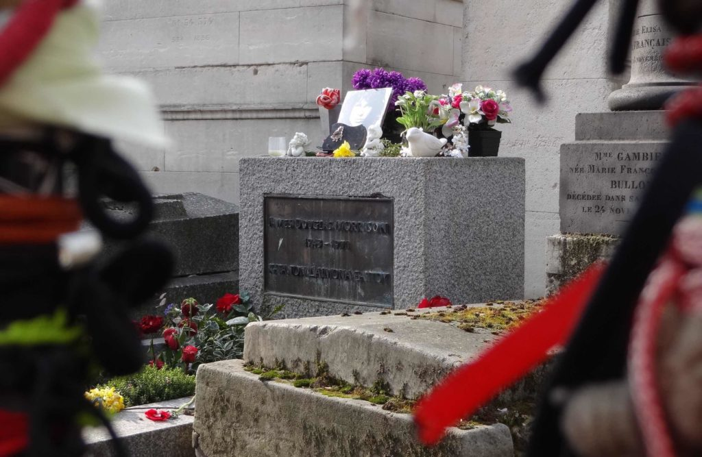 Jim 'The Doors' Morrison's cleaned-up grave stone seen through the bars of the barricade