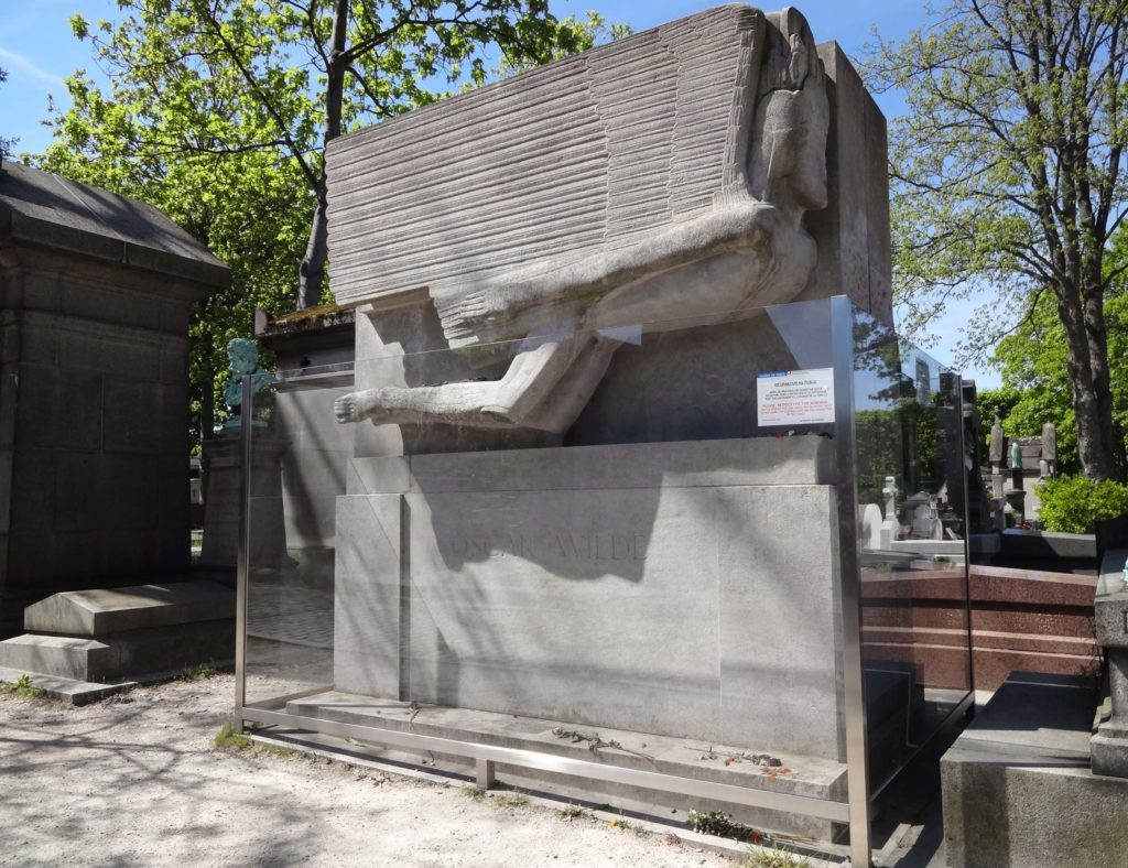 Oscar Wilde's head stone designed by Jacob Epstein appears to sit in a large, empty fish tank to protect it from graffiti