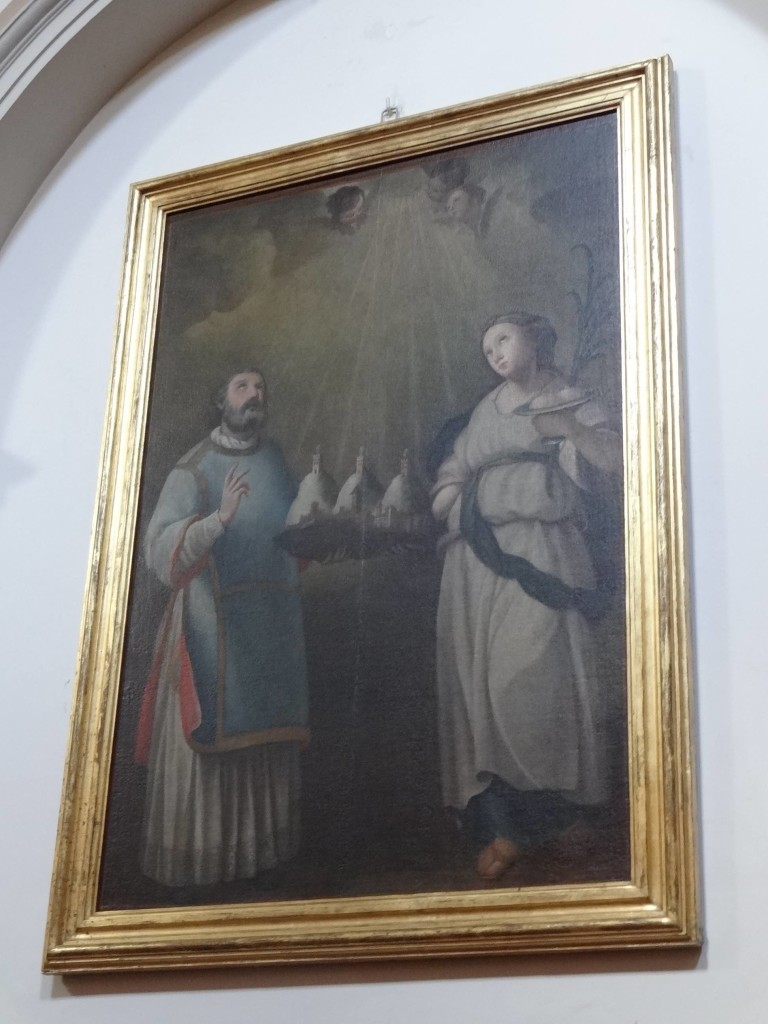 The painting of Saint Agatha used to celebrate San Marino's liberation in 1740. Saint Marinus standing to the left, is holding San Marino in his hand, symbolised by the three fortress towers found on top of Mount Titano