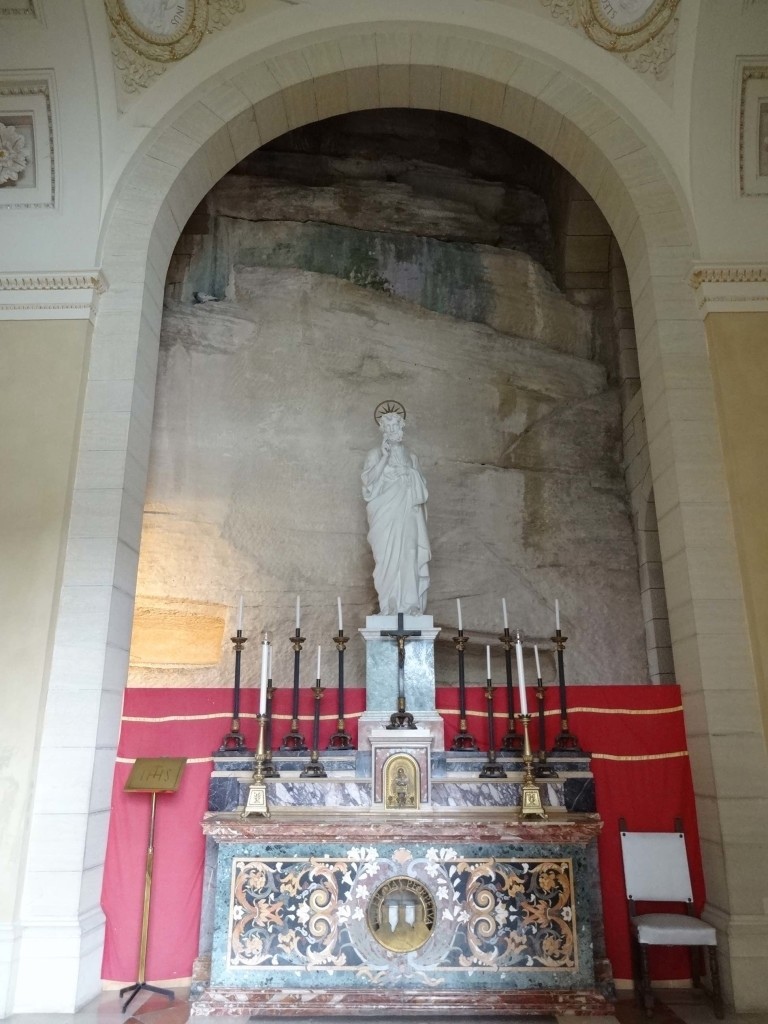 The two rectangular 'bed' cavities carved into the rock can be seen on either side of the statue of Saint Peter and just above the rim of the red curtain. One is directly behind the candles on the right and one is partially obscured by the arch but is lit up, to the left of the candles on the left