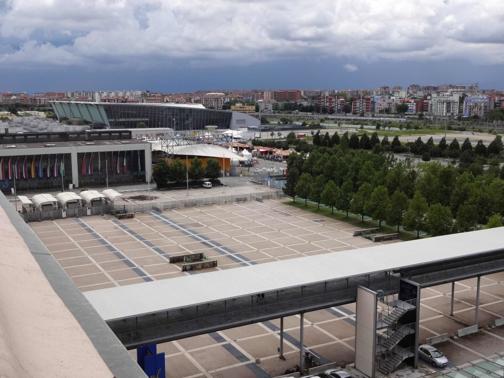 The view over the side: the factory car park (notably no Minis in sight) and in the distance the Oval Lingotto Olympic Arena built specifically to host the speed-skating events during the 2006 Winter Olympics. The arena is now used as an exhibition hall and the area around it is being developed (Summer 2014) into an affordable housing complex