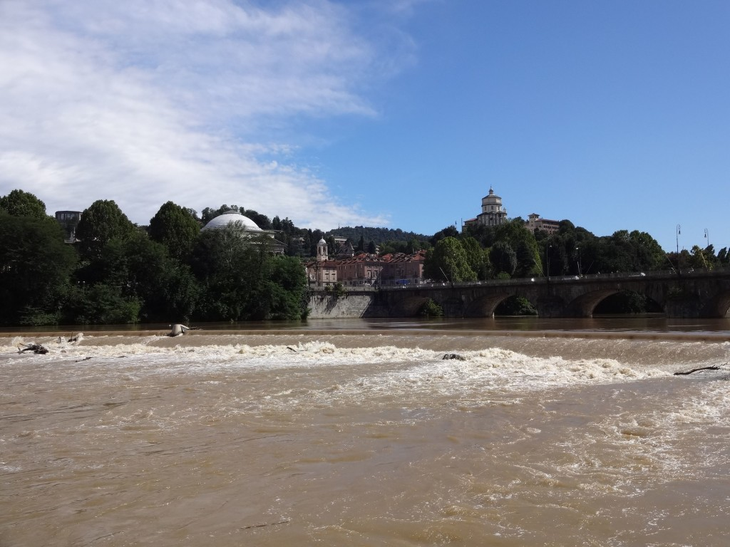 A picturesque view of the bridge from the west bank of the River Po, and also a famous view; here, Croker's fleet of Minis crossed the weir on the final stage of their Italian Job getaway within the city. The domed roof of the Chiesa di Gran Madre can just be seen poking above the tree tops centre left, and the tower seen centre right is ...