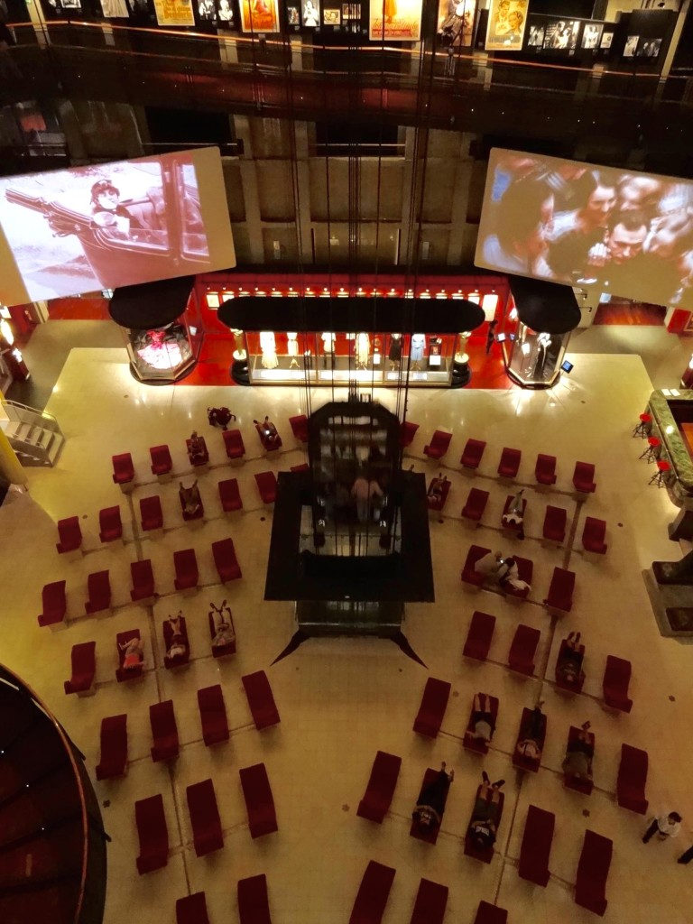 The panoramic lift/elevator ascending through the floor of the Mole's main hall. Rows of red recliners are available across the hall floor for anyone feeling faint on first seeing the shaftless lift/elevator in motion (clearly several people on this occasion felt the need to have a lie down for that very reason)
