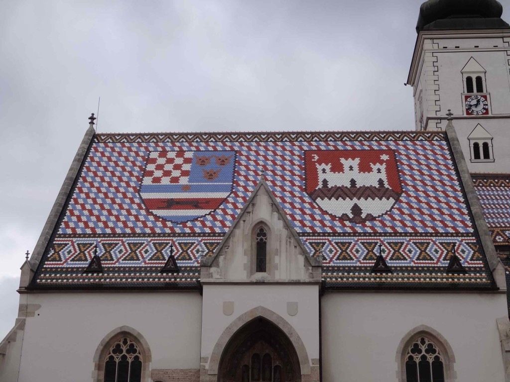 To the left is the medieval coat of arms of Croatia, Slavonia and Dalmatia, and to the right is the emblem of Zagreb